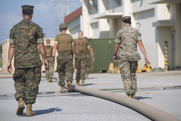 Marines inspect a fuel line during a line walk as part of the fuel support operations training Oct. 2, 2018 at Camp Hansen, Okinawa, Japan. Bulk fuel specialists walk along fuel hoses to inspect for leaks or holes in the line before transporting fuel or water. The bulk fuel specialists assembled fuel sites at Camp Hansen in order to practice fueling support operations for upcoming exercises and deployments. (U.S. Marine Corps photo by Lance Cpl. Armando Elizalde)