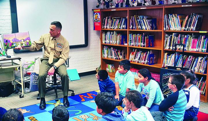 "MCINCR-MCBQ Commander Col. Joseph Murray sits in the Hampton Oaks Elementary Library reading the story ""Odd Velvet"" by Mary E. Whitcomb to first through fifth grade students."